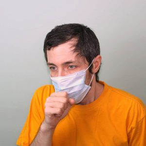 Middle-aged adult man in a yellow T-shirt on a gray background in a medical mask sneezes covering his face with his hand. Cough, fever. Disease protection coronavirus epidemic problem from China.
